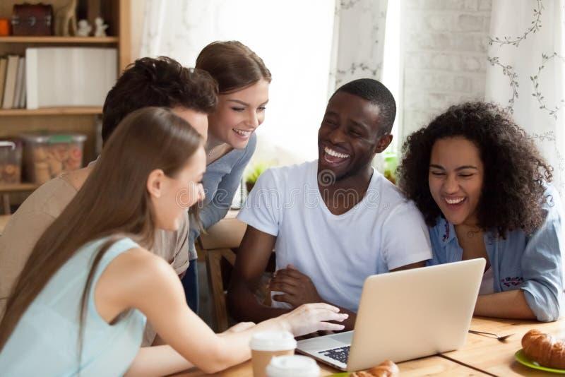 Amigos diversos felizes que olham o filme da comédia, vídeo engraçado no portátil imagens de stock