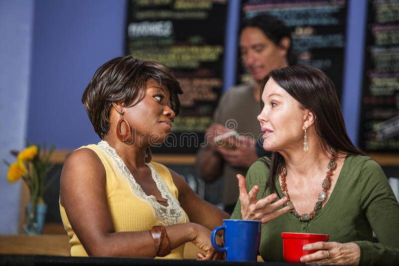 Amigos diversos que hablan en café imagenes de archivo