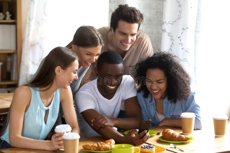 Amigos diversos que se divierten junto usando smartphone fotos de archivo