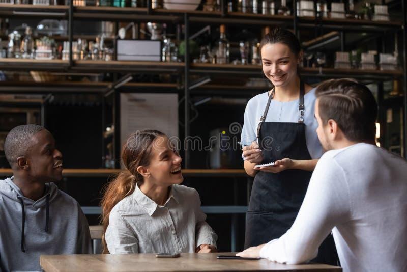 Amigos diversos que se sientan en el restaurante que pone la orden que habla con la camarera imágenes de archivo libres de regalías