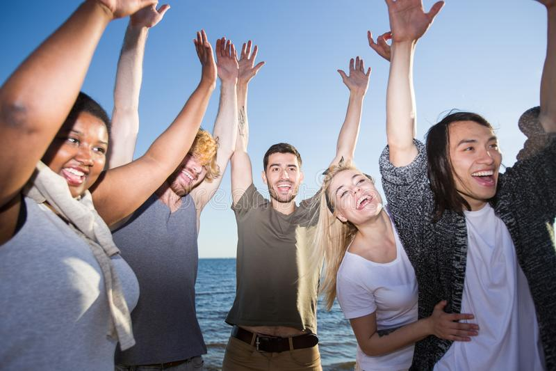 Amigos diversos que têm o divertimento na praia imagem de stock