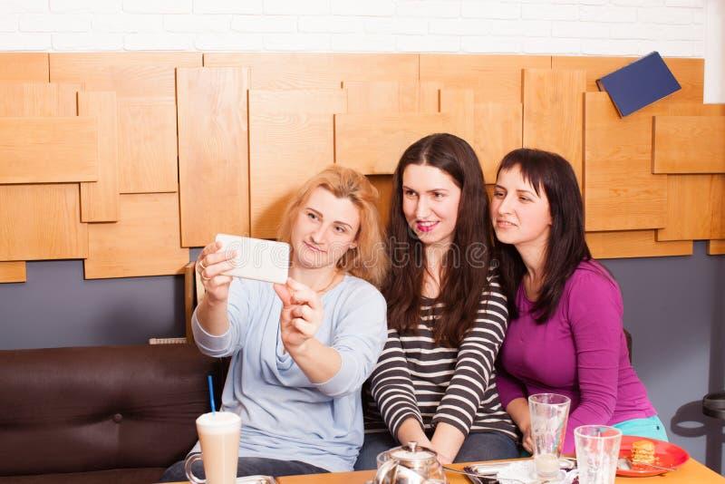 Amigos divertidos del selfie en un café imagen de archivo