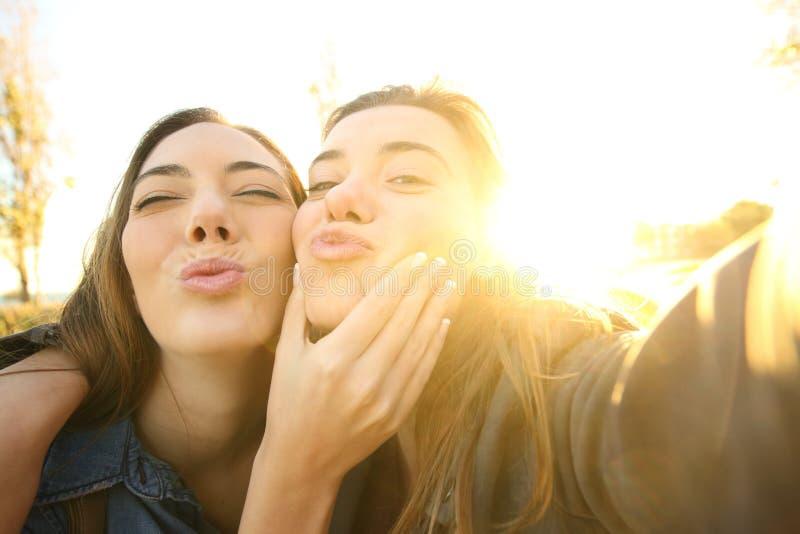Amigos divertidos que toman un selfie en la puesta del sol foto de archivo libre de regalías