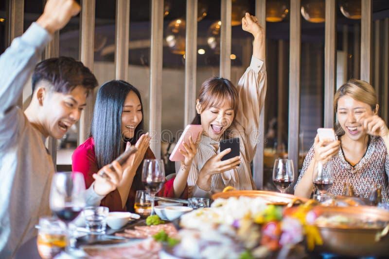 Amigos divirtiéndose en el restaurante y viendo el teléfono inteligente imagen de archivo libre de regalías