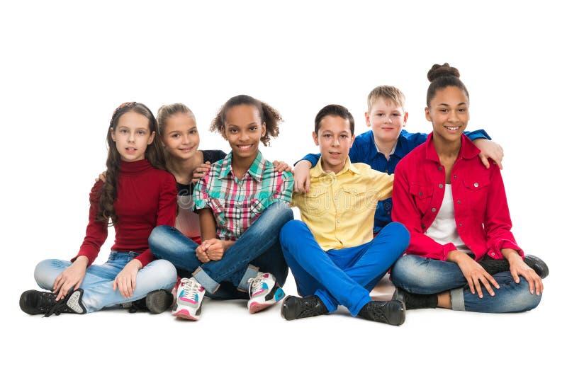 Amigos do adolescente que sentam-se no abraço do assoalho fotos de stock royalty free