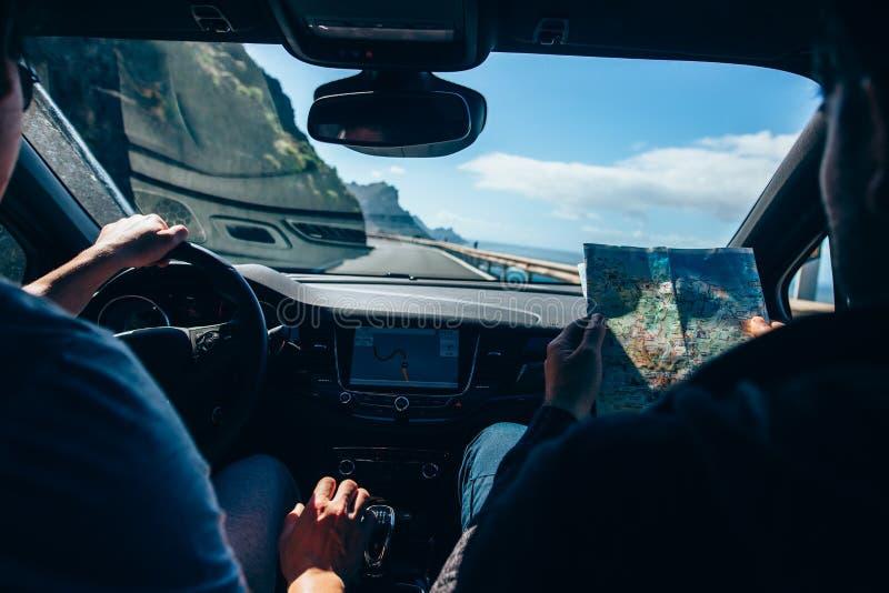 Amigos do viajante que conduzem o carro na estrada da montanha e que usam o mapa foto de stock royalty free