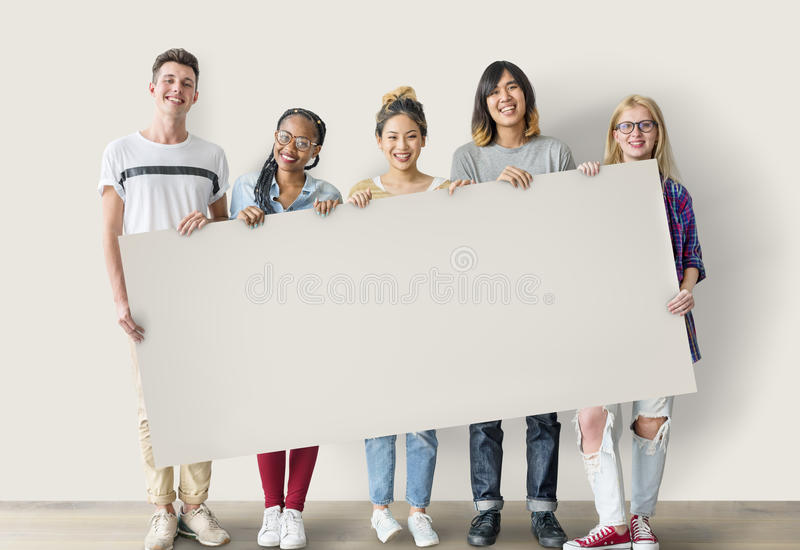 Amigos dos estudantes da diversidade que guardam o conceito da placa fotografia de stock royalty free