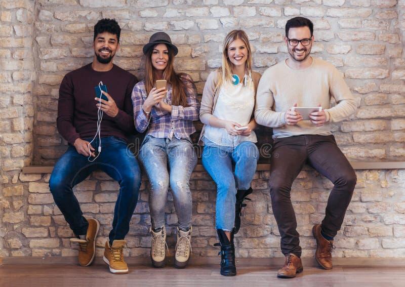 Amigos dos estudantes da diversidade que usam o conceito dos dispositivos de Digitas imagens de stock royalty free