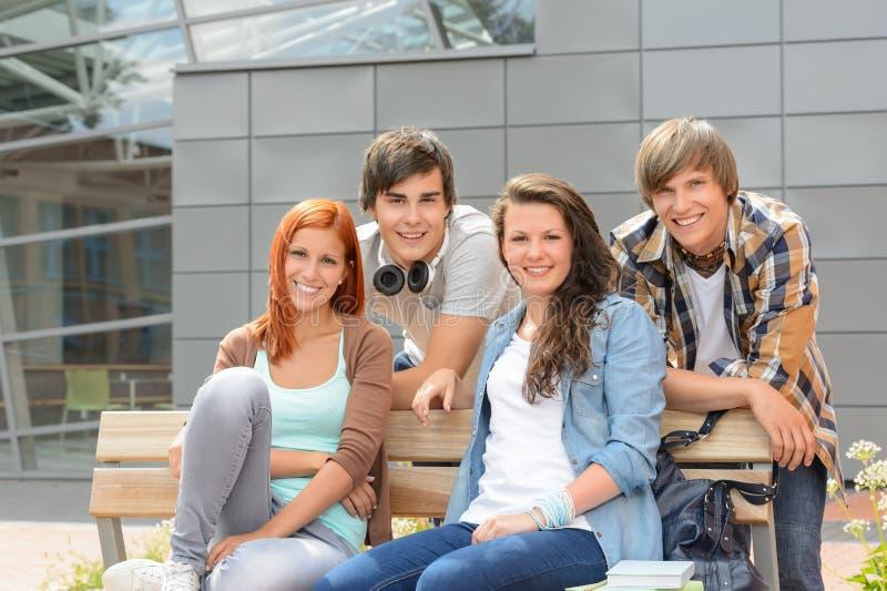 Amigos dos estudantes que sentam o banco fora do terreno imagens de stock