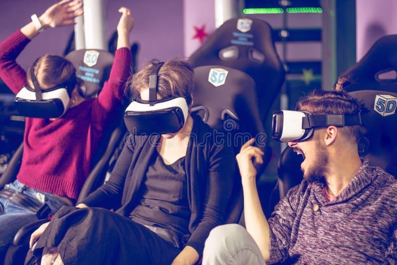 Amigos em óculos virtuais assistindo filmes no cinema com efeitos especiais em 5d fotografia de stock royalty free