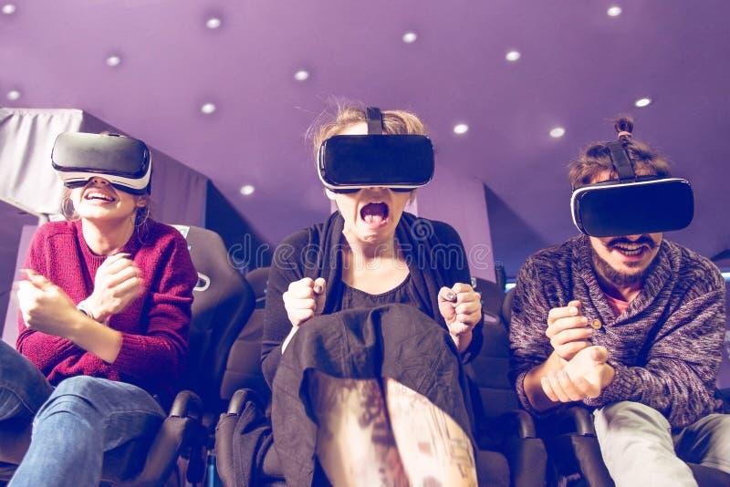 Amigos em óculos virtuais assistindo filmes no cinema com efeitos especiais em 5d imagens de stock royalty free