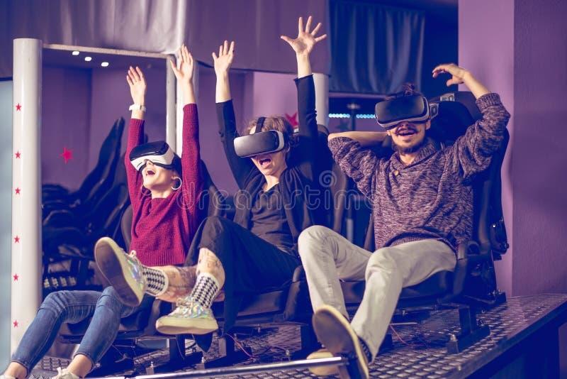 Amigos em óculos virtuais assistindo filmes no cinema com efeitos especiais em 5d foto de stock