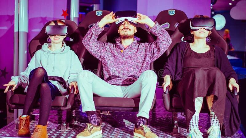 Amigos em óculos virtuais assistindo filmes no cinema com efeitos especiais em 5d foto de stock royalty free