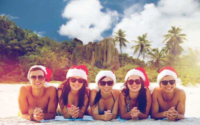 Amigos em chapéus de Santa na praia no Natal foto de stock royalty free
