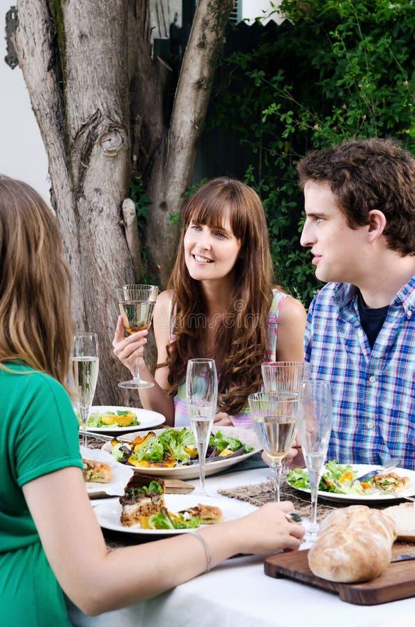 Amigos em um partido exterior no jardim com alimento e bebida imagens de stock