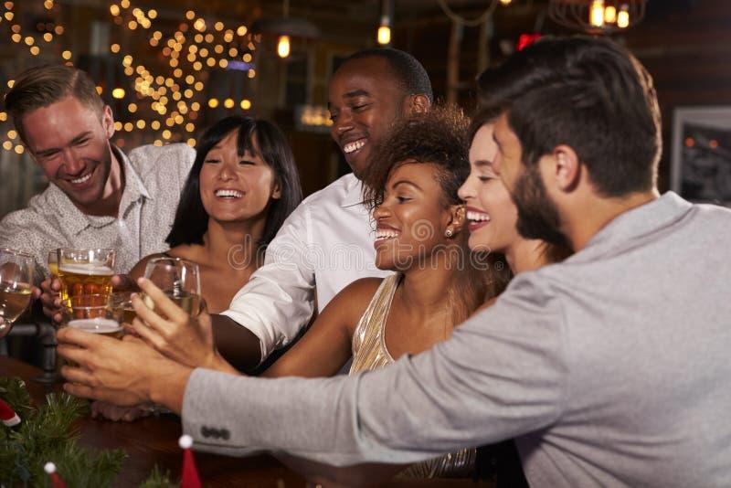 Amigos em uma festa de Natal que faz um brinde na barra fotos de stock