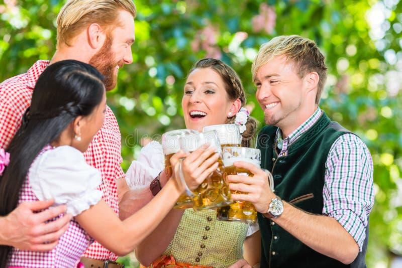 Amigos em vidros do tinido do jardim da cerveja com cerveja foto de stock royalty free