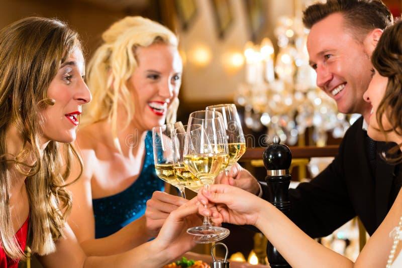 Amigos em vidros muito bons de um clink do restaurante imagens de stock royalty free