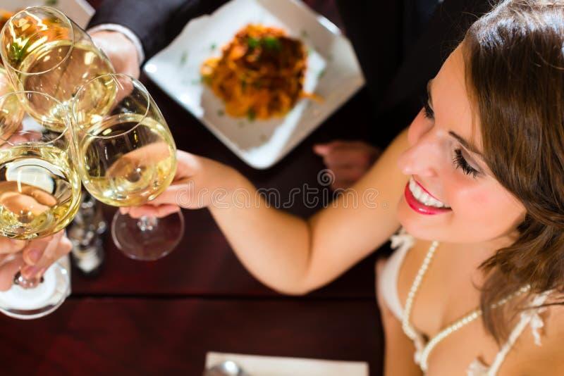 Amigos em vidros muito bons de um clink do restaurante foto de stock royalty free