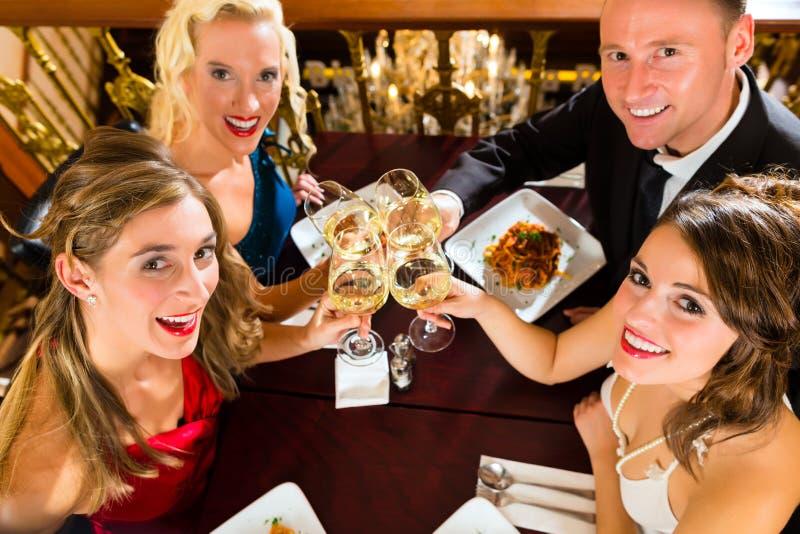 Amigos em vidros muito bons de um clink do restaurante fotos de stock