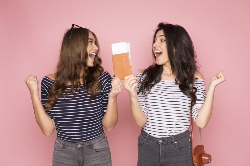 Amigos emocionados de las mujeres que sostienen boletos y el pasaporte fotos de archivo libres de regalías
