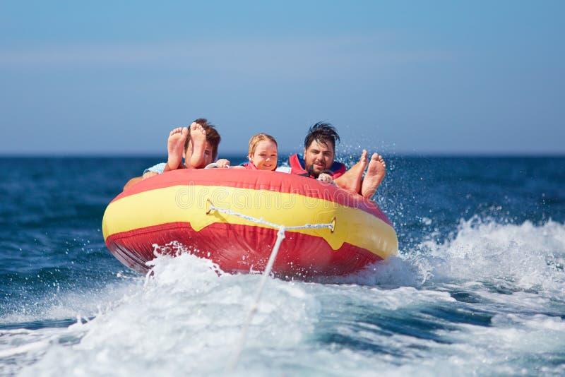 Amigos emocionados, familia que se divierte, montando en el tubo del agua durante vacaciones de verano imágenes de archivo libres de regalías