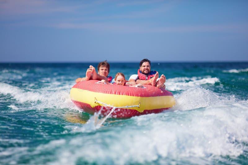 Amigos emocionados, familia que se divierte, montando en el tubo del agua durante vacaciones de verano imagen de archivo