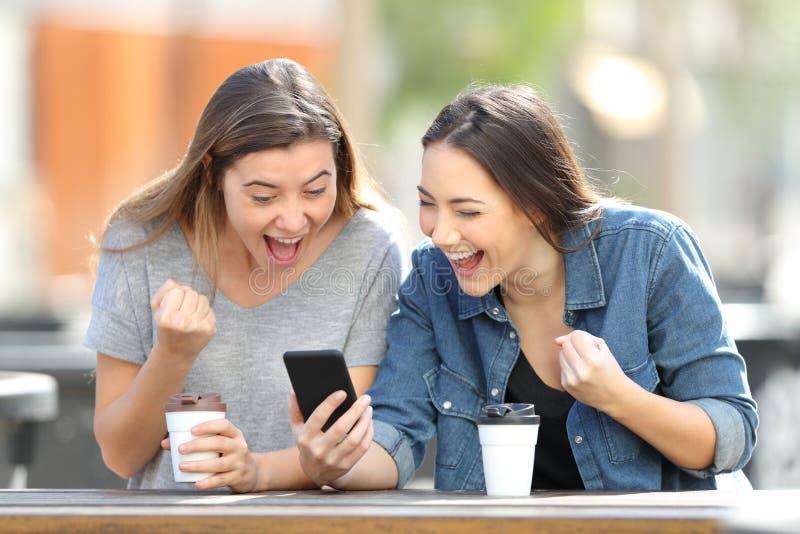 Amigos emocionados que celebran noticias en línea en el teléfono imagen de archivo libre de regalías