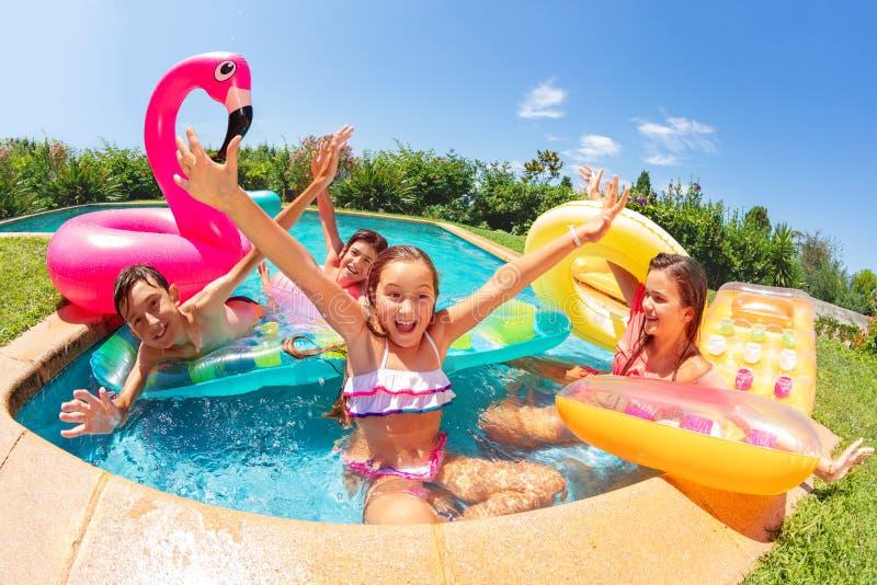 Amigos emocionados que juegan a juegos de la piscina en verano fotos de archivo libres de regalías