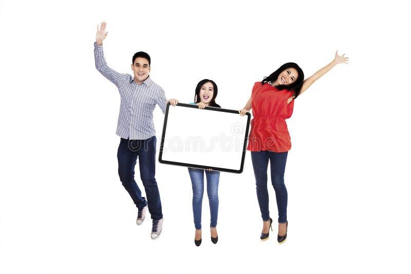 Amigos emocionados que muestran la bandera en blanco fotografía de archivo libre de regalías