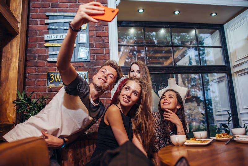 Amigos emocionados que toman el selfie con el smartphone que se sienta en la tabla que tiene noche hacia fuera fotografía de archivo libre de regalías