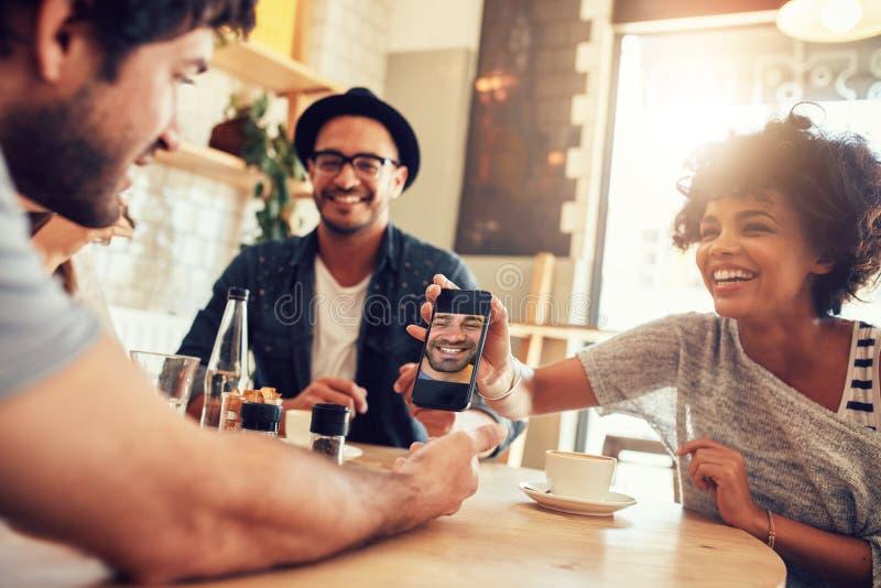 Amigos en café y mirada de las fotos en el teléfono elegante foto de archivo libre de regalías