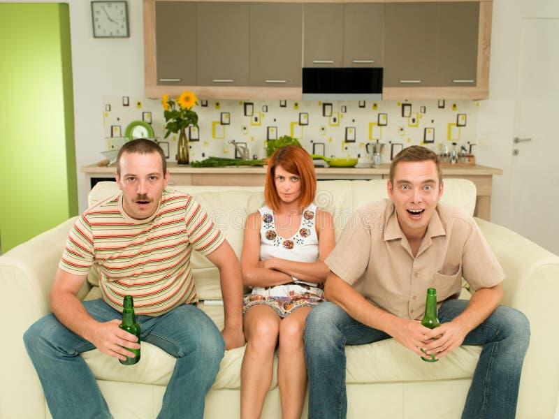 Amigos en casa que ven la TV imagen de archivo
