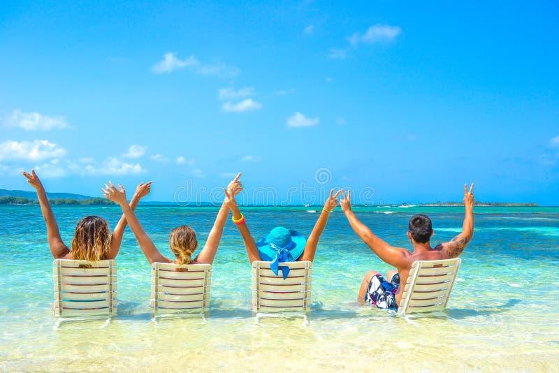 Amigos en días de fiesta en la playa imagenes de archivo