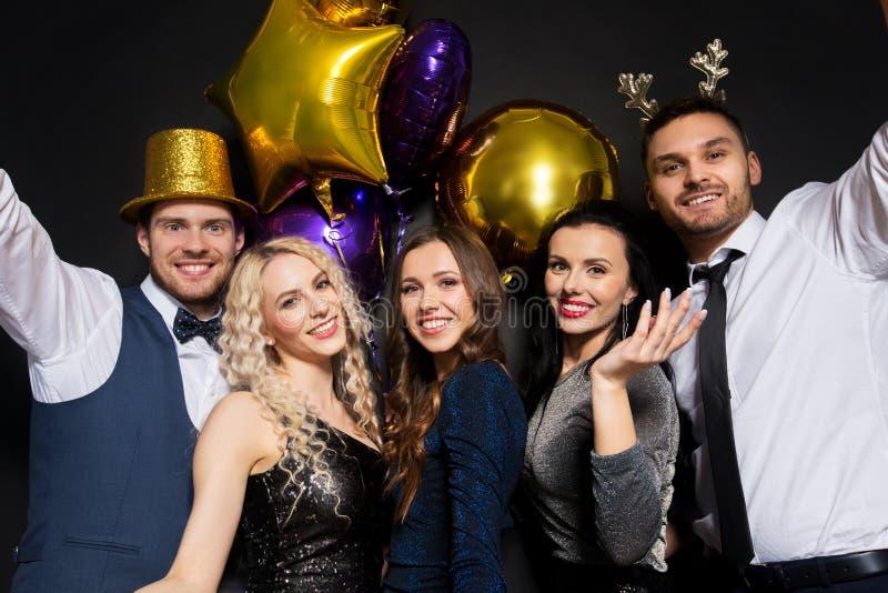 Amigos en el partido de la Navidad o del Año Nuevo fotos de archivo libres de regalías