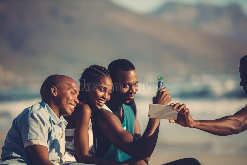 Amigos en el partido de la playa que toma el selfie imagenes de archivo
