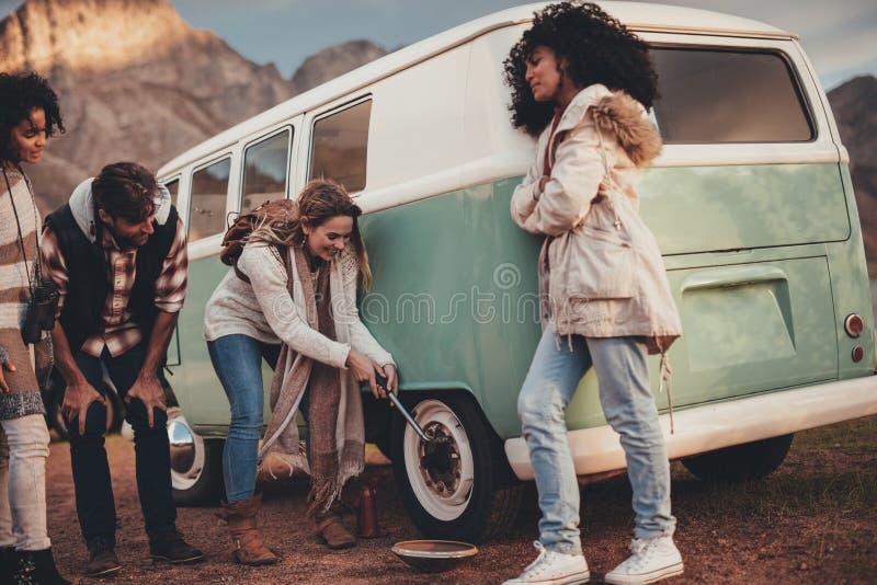 Amigos en el viaje por carretera que repara la puntura del neumático de la furgoneta imagenes de archivo