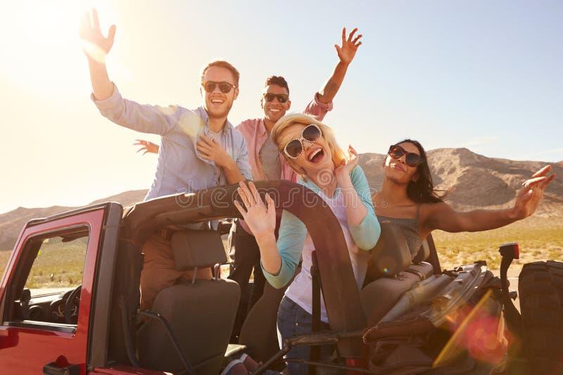 Amigos en el viaje por carretera que se coloca en coche convertible fotos de archivo