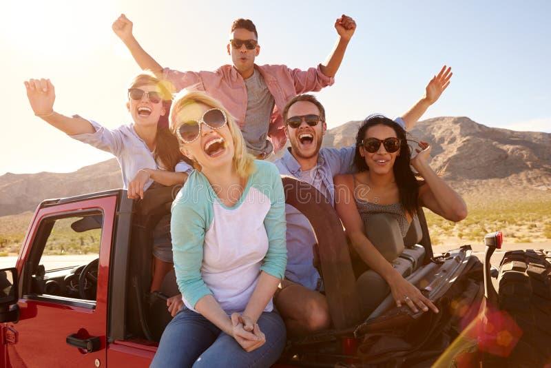 Amigos en el viaje por carretera que se coloca en coche convertible imagen de archivo