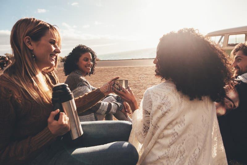 Amigos en el viaje por carretera que se relaja al aire libre y el café de consumición imagen de archivo libre de regalías
