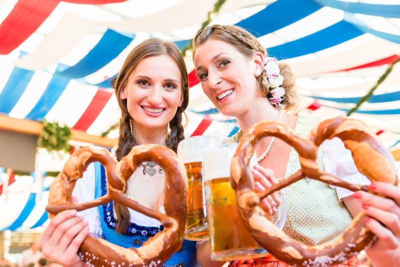 Amigos en la feria bávara con los pretzeles gigantes imagen de archivo