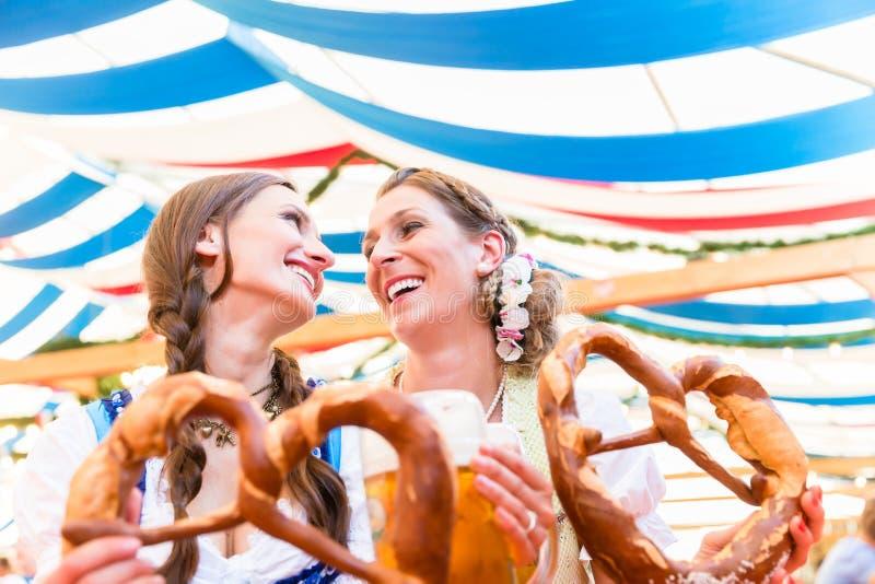 Amigos en la feria bávara con los pretzeles gigantes imagenes de archivo