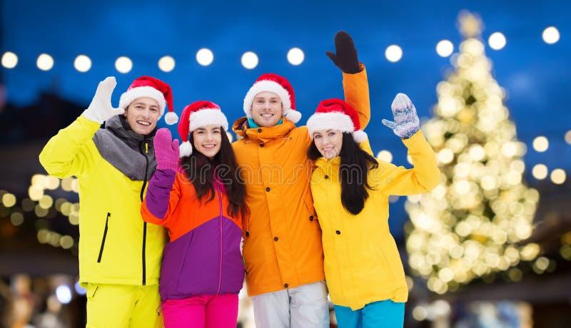 Amigos en los sombreros de santa y los trajes de esquí en la Navidad imagenes de archivo