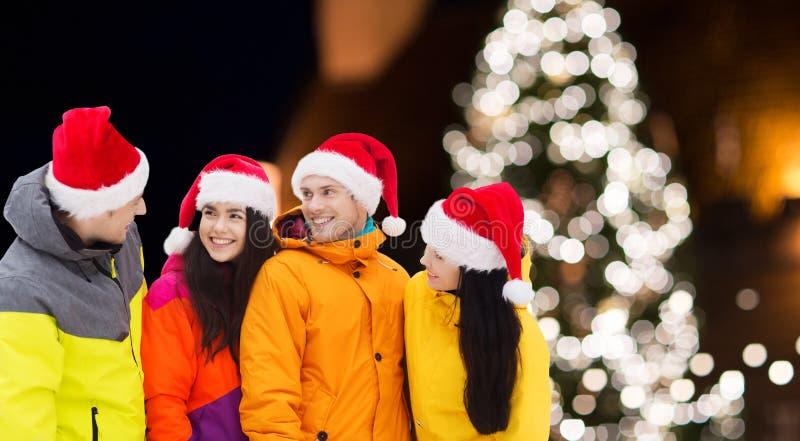 Amigos en los sombreros de santa y los trajes de esquí en la Navidad fotos de archivo libres de regalías