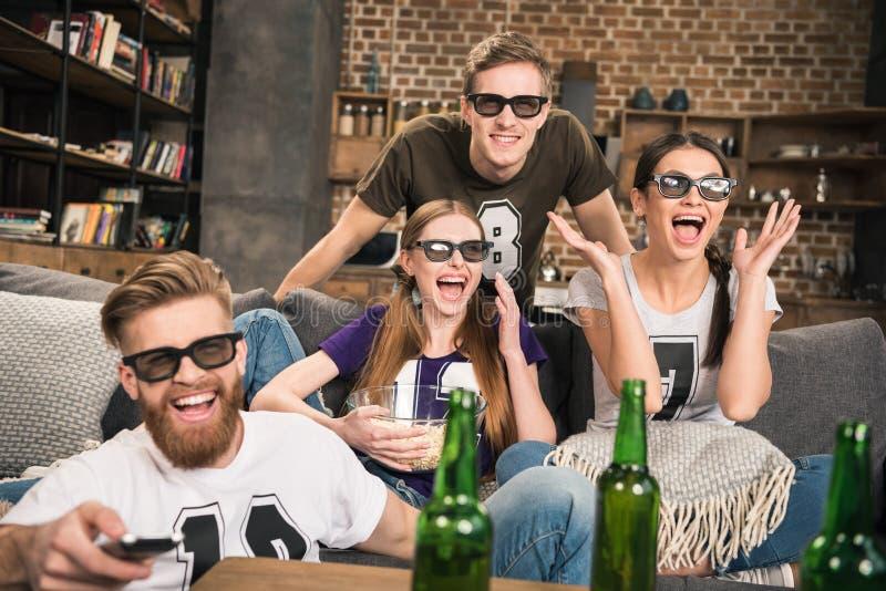 Amigos en los vidrios 3D que miran película fotos de archivo