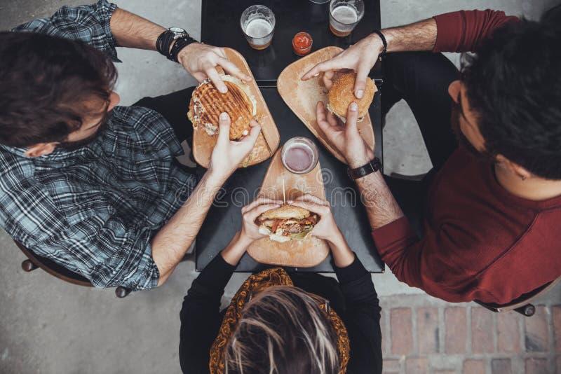 Amigos en restaurante de los alimentos de preparación rápida fotos de archivo libres de regalías