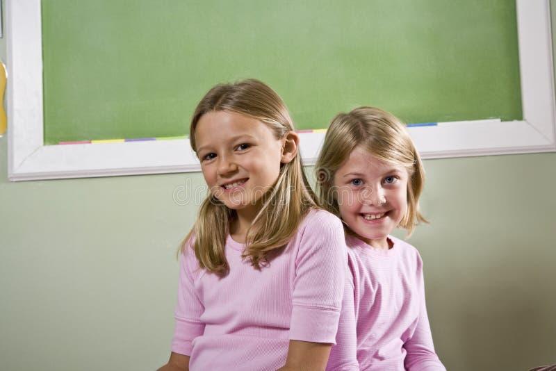 Amigos en sala de clase de la escuela fotos de archivo