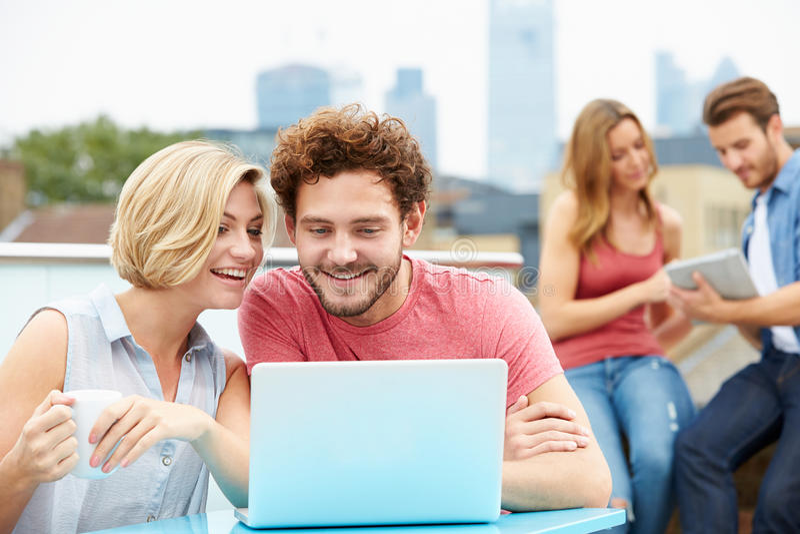 Amigos en terraza del tejado usando el ordenador portátil y la tableta de Digitaces foto de archivo libre de regalías
