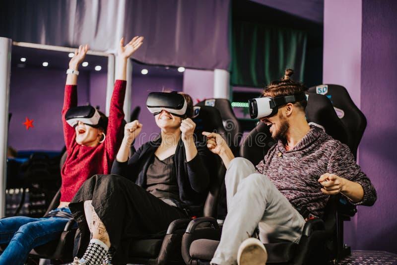 Amigos en vidrios virtuales que miran películas en el cine con el SP imagen de archivo