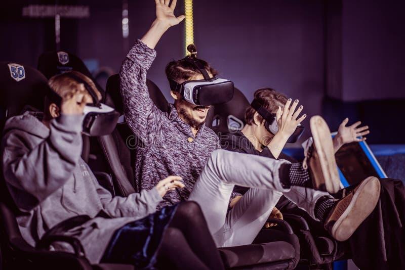 Amigos en vidrios virtuales que miran películas en el cine con el SP imagenes de archivo